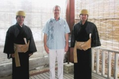 Staff wearing traditional ancient palace garb and President Woodward in a typical Okinawa shirt for business or casual wear, a gift from Dr. Oshiro of Eiken.